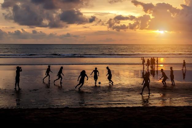 Schattenbild der einheimischen, die fußball bei sonnenuntergang spielen.