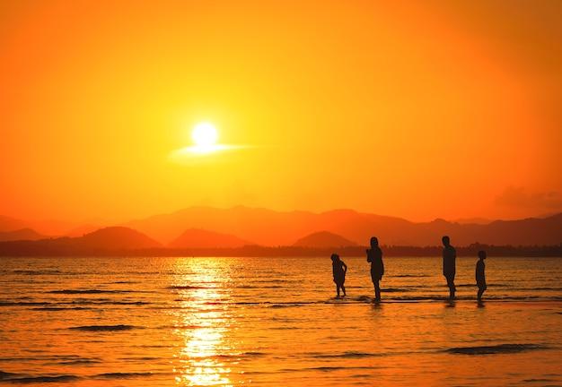 Schattenbild der familie auf dem strand bei sonnenuntergang