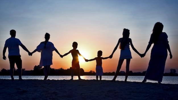 Schattenbild der familie auf sonnenuntergang