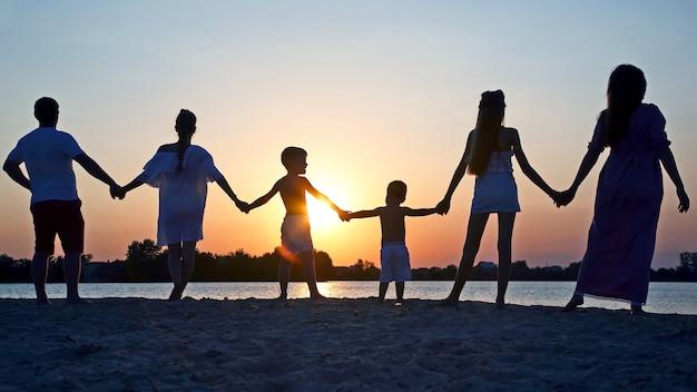 Schattenbild der familie auf sonnenunterganghintergrund
