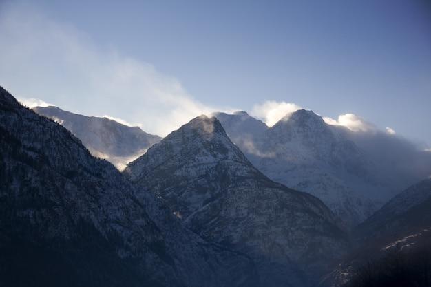 Schattenbild der felsigen berge bedeckt mit schnee und nebel während des winters