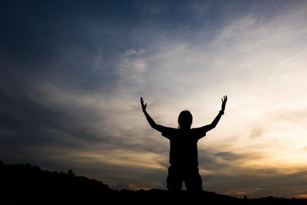 Schattenbild der frau betend mit gott