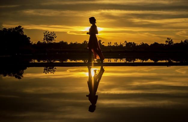 Schattenbild der frau, die am strand während des schönen sonnenuntergangs geht