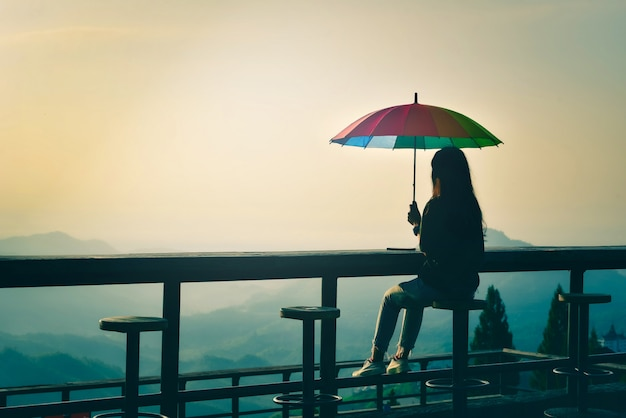 Schattenbild der frau, die auf stuhl sitzt, halten bunten regenschirm, der neblig in den bergen mit dramatischem himmel bei sonnenaufgang schaut. retro- und vintage-stil