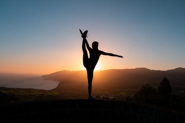 Schattenbild der frau, die die freiheit genießt, die sich bei sonnenuntergang mit bergen und meer glücklich fühlt