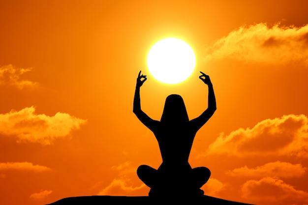 Schattenbild der frau, die yoga während des sonnenuntergangs am meer praktiziert.
