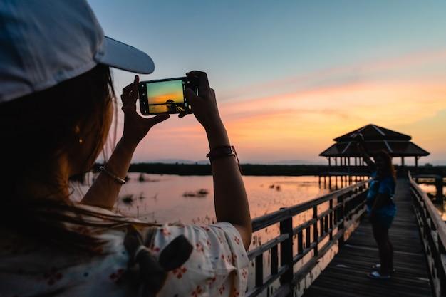 Schattenbild der frau foto ihres freundes machend, der auf holzbrücke auf sonnenuntergang in nationalpark khao sam roi yot steht. thailand.