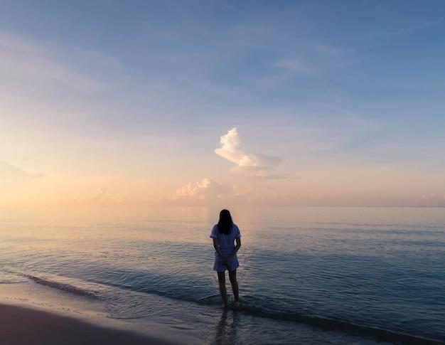 Schattenbild der frau gehend auf den strandhintergrund mit weinlesefilter