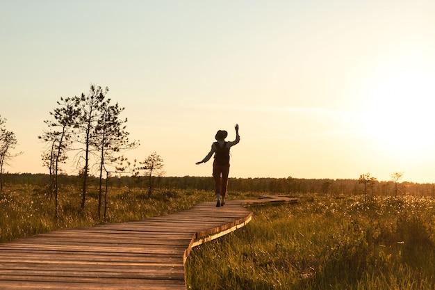 Schattenbild der frau mit rucksack auf wanderweg im sommer im freien. naturforscher genießt die natur und einen moment bei sonnenuntergang auf dem weg