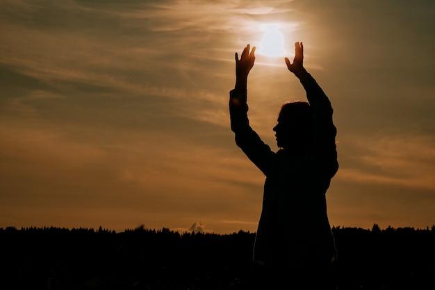 Schattenbild der frau sonnenuntergang genießend. eine frau in einem weizenfeld macht fließende bewegungen. das konzept der ruhe und meditation