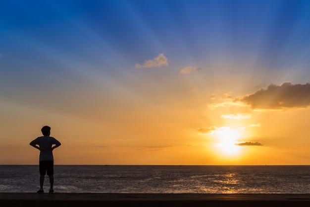 Schattenbild der frauen, die am strand mit sonnenunterganghintergrund stehen