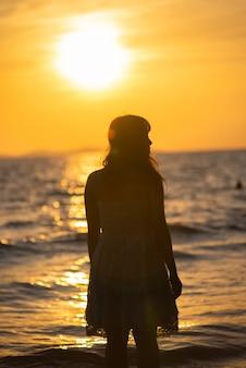 Schattenbild der freien frau die freiheit genießend, die auf dem strand glücklich sich fühlt.