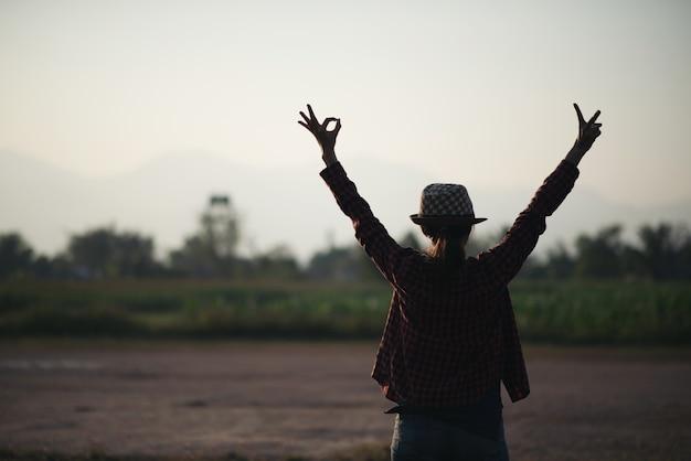 Schattenbild der freien frau die freiheit genießend, die bei sonnenuntergang glücklich sich fühlt