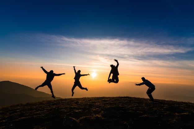 Schattenbild der freunde, die im sonnenuntergang für glück, spaß und teamarbeitskonzept springen