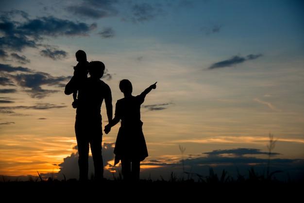 Schattenbild der glücklichen eltern der familie, die spaß haben