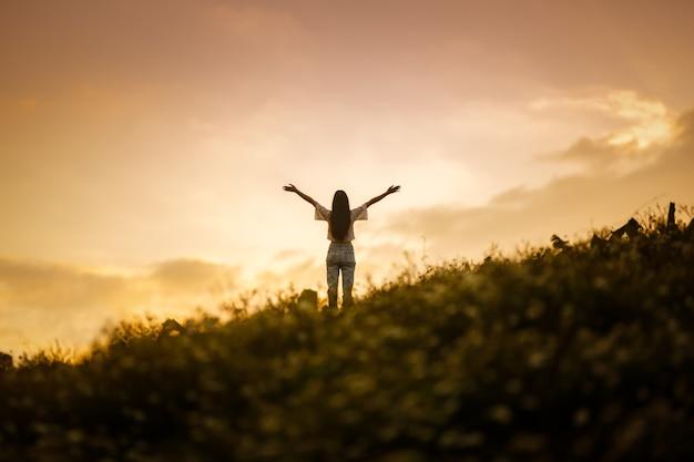 Schattenbild der glücklichen frau, die auf berghügel im sommer sonnenunterganghimmel entspannt