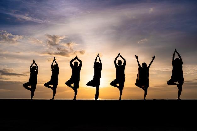 Schattenbild der gruppe von personen yoga während des bunten sonnenuntergangs oder des sonnenaufgangs an einem strand tuend