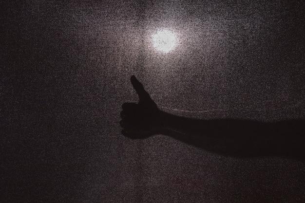 Schattenbild der hand daumen gestikulierend