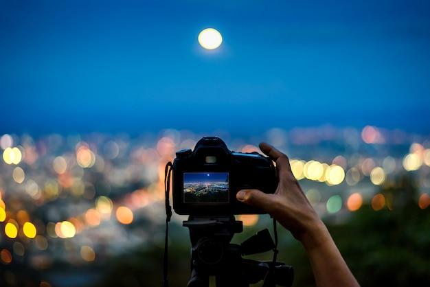 Schattenbild der hand, die foto mit dslr kamera auf stativ in der nachtlichtstadt von den bergen macht