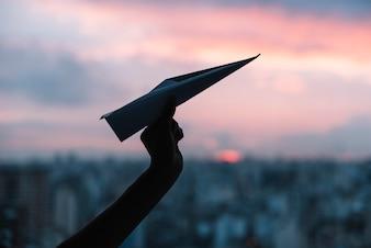 Schattenbild der Hand einer Person, die Papierflugzeug gegen drastischen Himmel hält