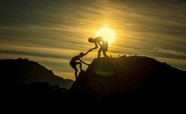 Schattenbild der helfenden hand zwischen bergsteiger mit zwei jungen