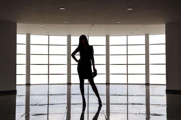 Schattenbild der jungen attraktiven frau, die im anzug mit einem kurzen rock gekleidet wird, steht gegen das große leere fenster in einem weißen büro und hält ein anmerkungsbuch.
