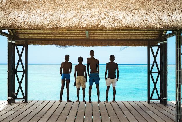 Schattenbild der jungen, die am strand in den sommerferien entspannen