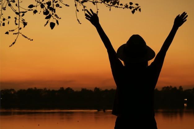Schattenbild der jungen frau arme gegen schönen orange farbsonnenunterganghimmel auf dem seeufer anhebend