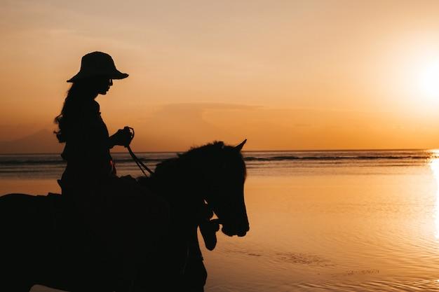 Schattenbild der jungen frau, die auf einem pferderücken am strand während des goldenen bunten sonnenuntergangs nahe meer reitet