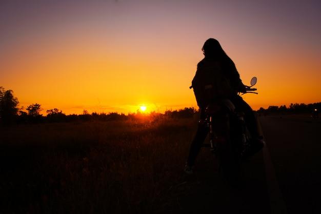 Schattenbild der jungen frau fahren mit motorrad auf der straße und genießen freiheit und aktives leben
