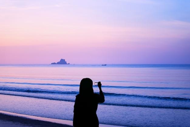 Schattenbild der jungen frau fotos der landschaft bei sonnenaufgang machend.
