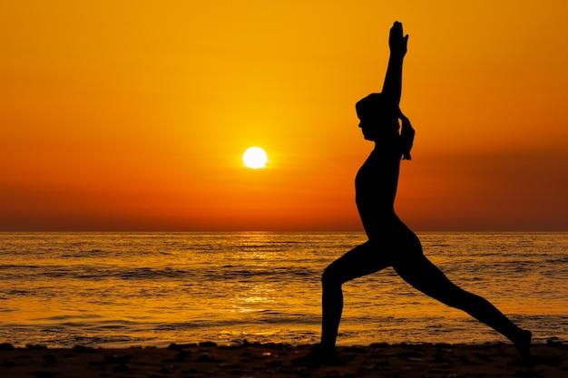 Schattenbild der jungen frau in einem yogianzug, der yoga am strand in der sonnenuntergangszeit tut.