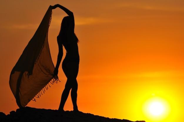 Schattenbild der jungen schlanken frau im bikini stehend und hält pareo in erhöhten händen bei sonnenuntergang am sommertag mit buntem himmel