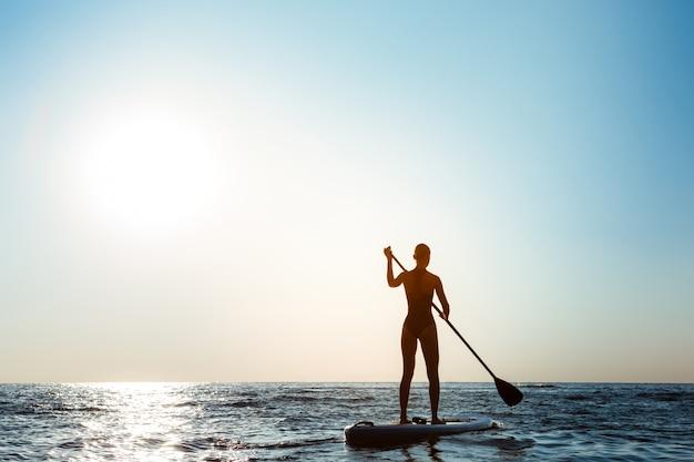 Schattenbild der jungen schönen frau, die im meer bei sonnenaufgang surft.