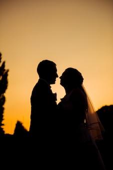 Schattenbild der jungvermählten, die bei sonnenuntergang küssen