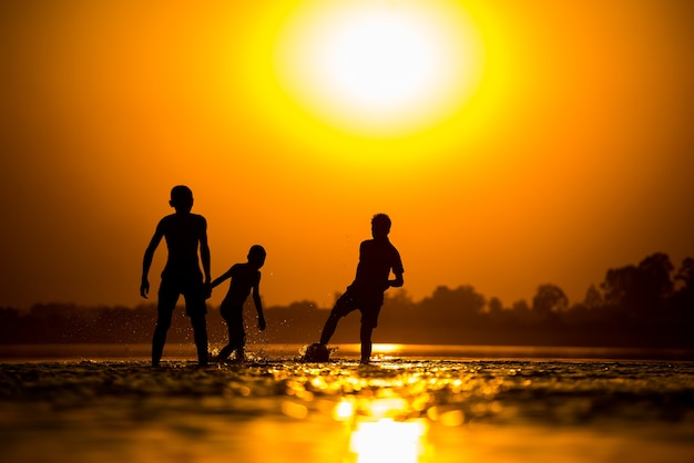 Schattenbild der kinder, die fußball auf dem strand spielen