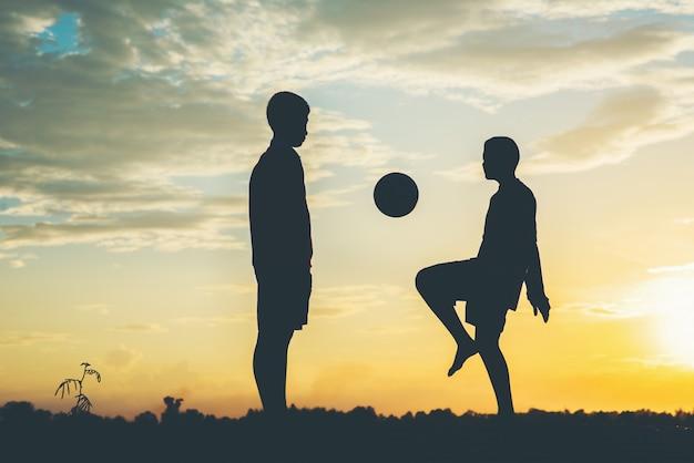 Schattenbild der kinder spielen fußballfußball