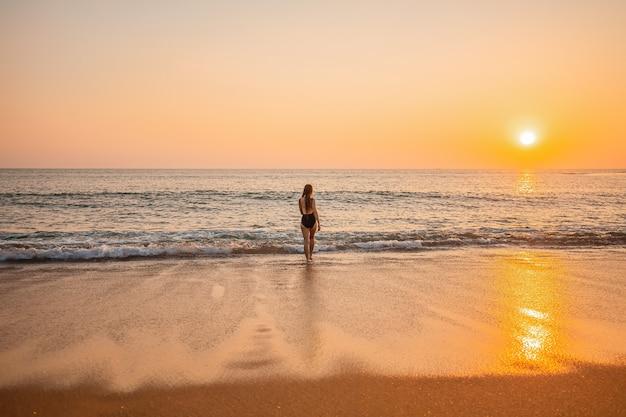 Schattenbild der langen haarfrau sonnenuntergang am strand auf phuket, thailand genießend