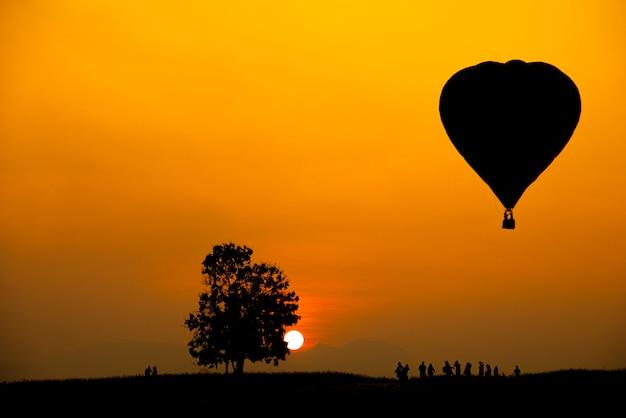 Schattenbild der leute, des baumes und des heißluftballons auf einem bunten sonnenuntergang mit großer sonne.