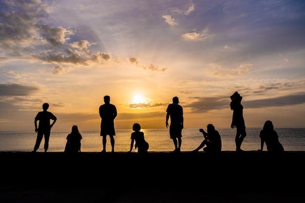 Schattenbild der leute, die bunten sonnenaufgang an einem strand aufpassend sich entspannen
