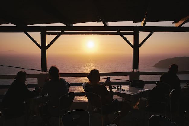 Schattenbild der leute, die ihre zeit am sonnenuntergang in einem café am potamos-strand, griechenland genießen