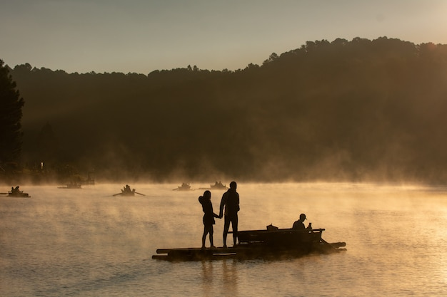 Schattenbild der liebhaberleute, die auf das floß am reservoirmorgen handeln