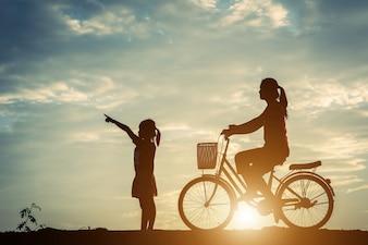 Schattenbild der Mutter mit ihrer Tochter und Fahrrad