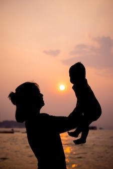 Schattenbild der mutter spielend mit ihrem kleinkind bei sonnenuntergang
