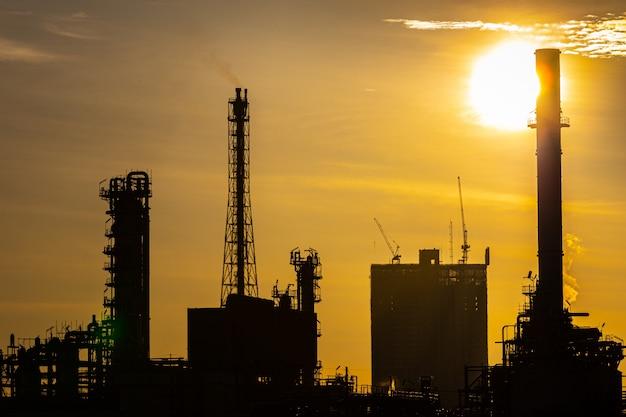 Schattenbild der öl- und gasraffinerieindustrieanlage mit funkelnbeleuchtung und -sonnenaufgang morgens