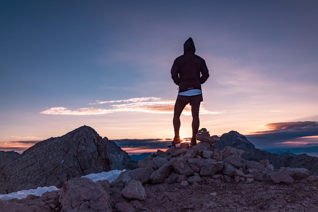 Schattenbild der person stehend auf den felsen, die sonnenuntergang aufpassen