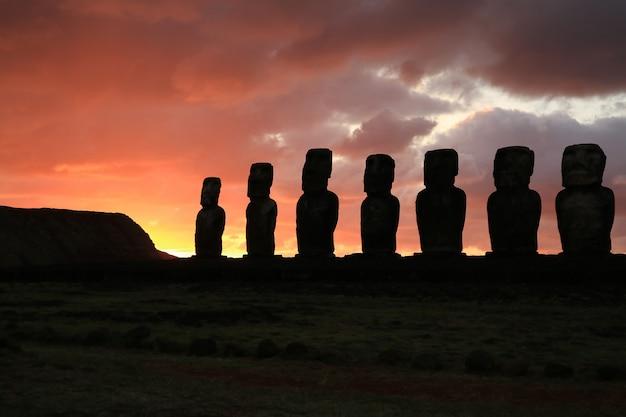 Schattenbild der riesigen moai-statuen von ahu tongariki gegen bewölkten himmel des schönen sonnenaufgangs,