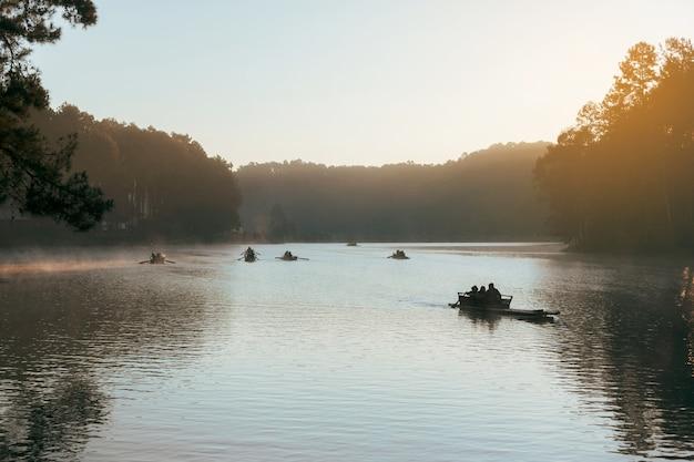 Schattenbild der romantischen reise, bambus-rafting auf dem see am morgen im pang ung-nationalpark, mae hong son thailand.