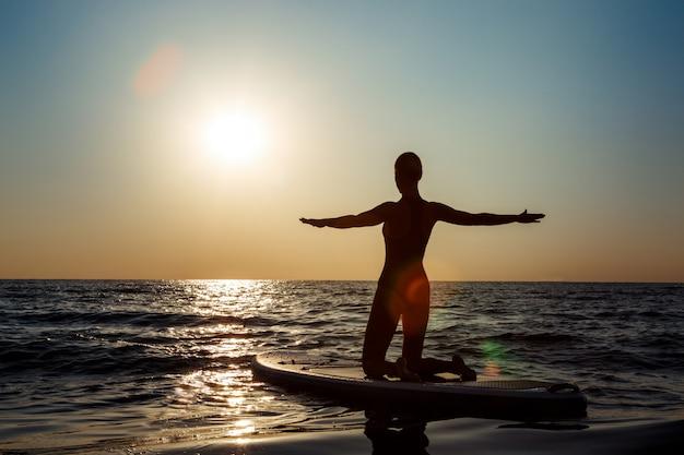 Schattenbild der schönen frau, die yoga auf surfbrett bei sonnenaufgang praktiziert.