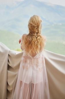 Schattenbild der schönen mädchenbraut im peignoir steht des balkons, der die berge übersieht